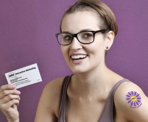 Girl wearing custom temporary tattoo and holding business card